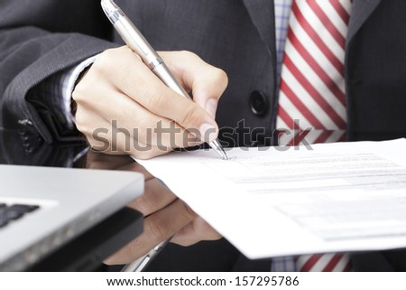 Businessman writing on a form in office