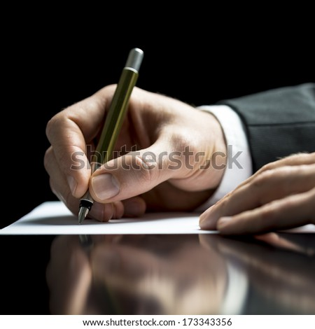 Businessman writing on a sheet of white paper with a fountain pen as he signs an agreement or contract, writes correspondence, takes notes or completes a questionnaire, closeup low angle view - stock photo