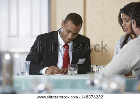 Businessman writing on document with coworkers sitting at desk in office - stock photo