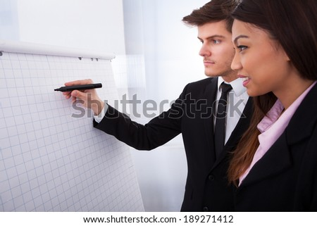 Businessman writing on flipchart with female colleague standing by him in office - stock photo