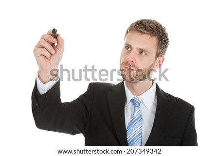 Businessman writing on invisible screen with marker over white background