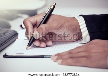 Businessman writing on notebook with pen in the office in vintage color tone