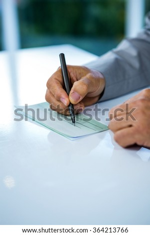 Businessman writing on paper in office