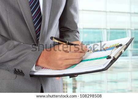 businessman writing on paper in the office