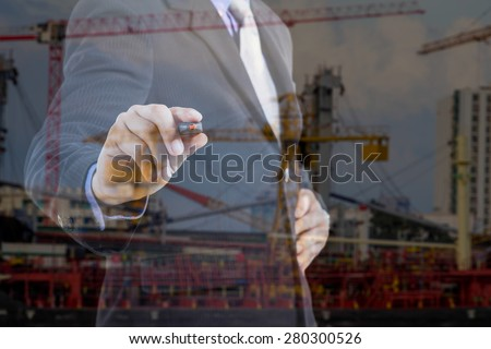 Businessman writing on window  behind the back of the businessman one can see the construction cranes - stock photo
