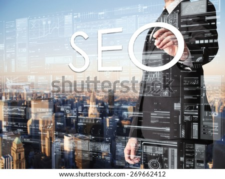 businessman writing SEO on transparent board with city in background  - stock photo