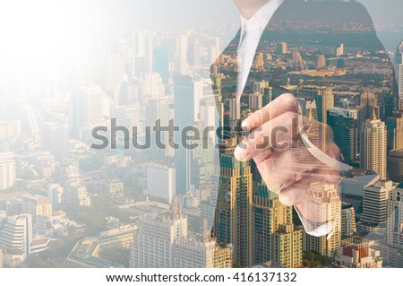 businessman writing something on transparent board with city reflection, double exposure - stock photo