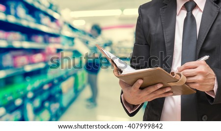 Businessman writing the note book on Abstract blurred photo of store in department store bokeh background - stock photo