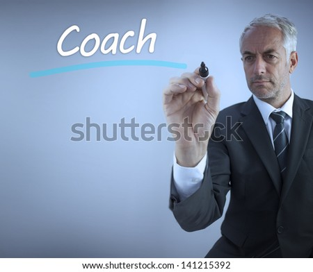 Businessman writing the word coach with a marker - stock photo