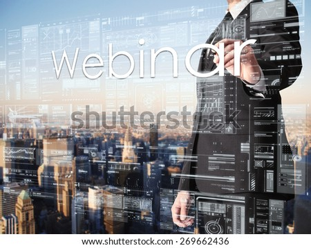 businessman writing Webinar on transparent board with city in background  - stock photo