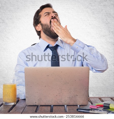 Businessman yawning in his office - stock photo
