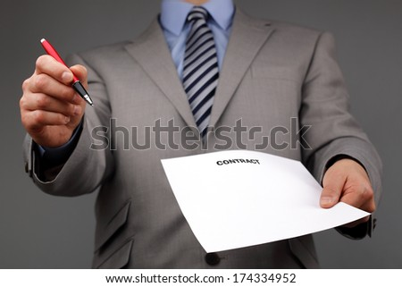 Businessmans hand holding a pen requesting a signature on a contract or document - stock photo