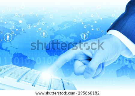 Businessmans hand touching keyboard on abstract blue background with world map