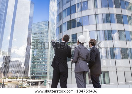 Businessmen and architect team outdoors planning construction project with office buildings - stock photo
