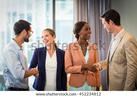 Businessmen and businesswomen shaking hands with each other in the office