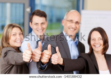 Businessmen and businesswomen showing thumbs up sign in office