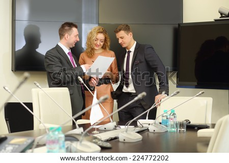 Businessmen and secretary discuss the document in conference hall - stock photo