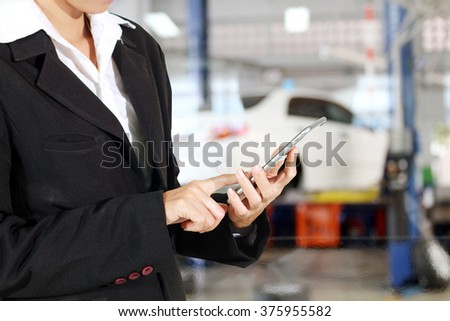 Businessmen and women are using mobile and touch smart phone and young female mechanic for mechanic inspecting on a car in auto repair shop - stock photo