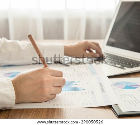 Businessmen are analyzed data from report and a laptop computer. - stock photo