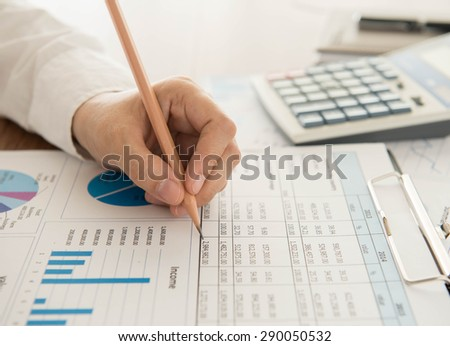 Businessmen are analyzing the data from the report. - stock photo