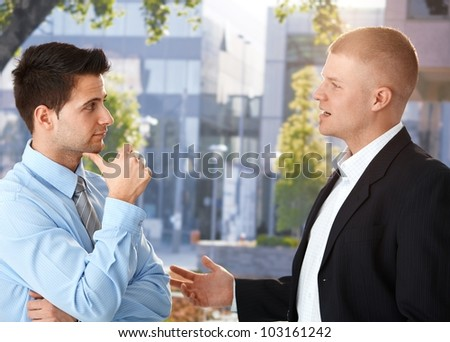 Businessmen chatting outside of office building, enjoying break. - stock photo