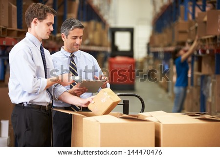 Businessmen Checking Boxes With Digital Tablet And Scanner - stock photo