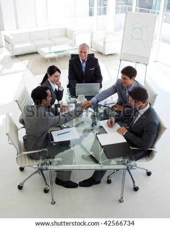 Businessmen closing a deal in a meeting with their associates - stock photo