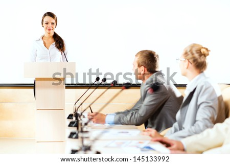 businessmen communicate at the conference, sitting at the table, focus on presenter