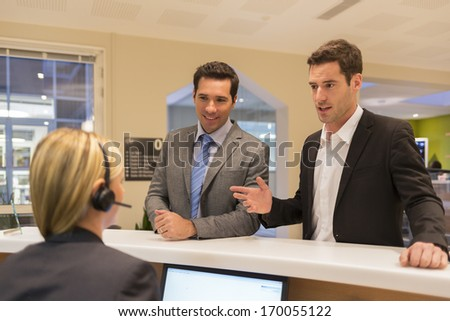 Businessmen communicating with female receptionist in lobby office - stock photo