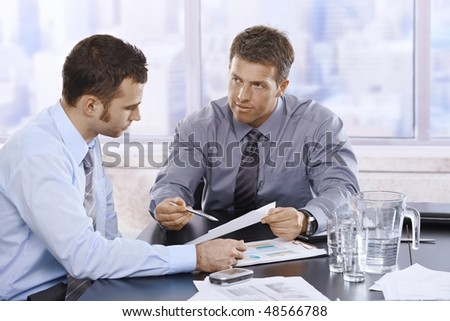Businessmen discussing business report sitting at meeting table in office. - stock photo