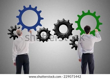 Businessmen drawing gear wheels - stock photo