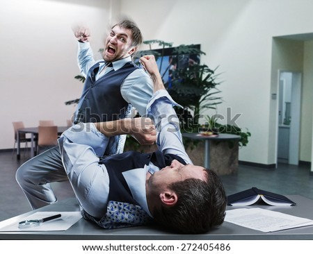 Businessmen fighting in the office - stock photo