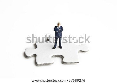 Businessmen figurines standing on and around puzzle pieces