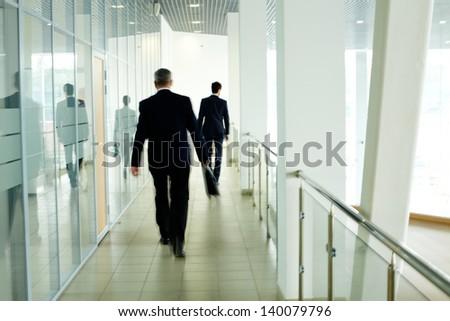 Businessmen going along corridor inside office building - stock photo