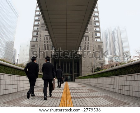Businessmen going to work in downtown Tokyo - stock photo