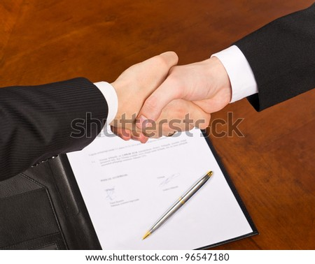 Businessmen hand shake after signing the agreement.