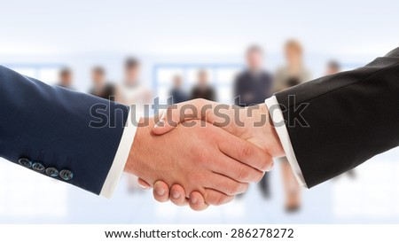 Businessmen hand shake with business people in background. Congratulation or cooperation concept - stock photo