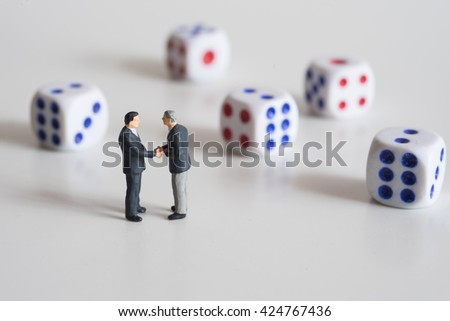 Businessmen hand shaking with dice. Business risk concept. - stock photo