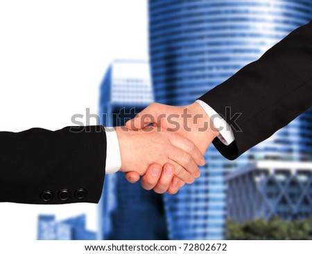 Businessmen Hand shaking with modern building background - stock photo