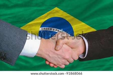 businessmen handshake after good deal in front of brazil flag - stock photo