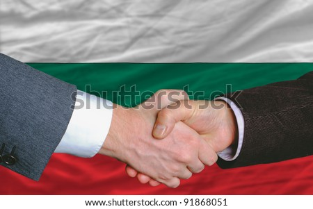 businessmen handshake after good deal in front of bulgaria flag - stock photo