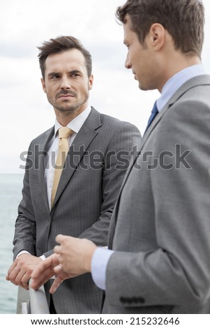 Businessmen having a discussion on terrace - stock photo