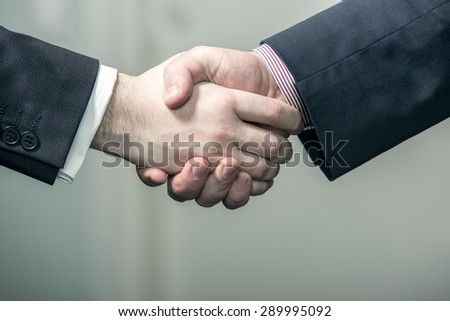 Businessmen holding hands in handshake
