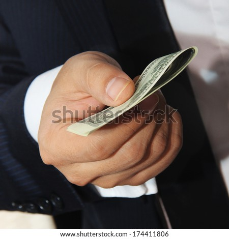 Businessmen holding money 100 dollars proposing it to you - stock photo