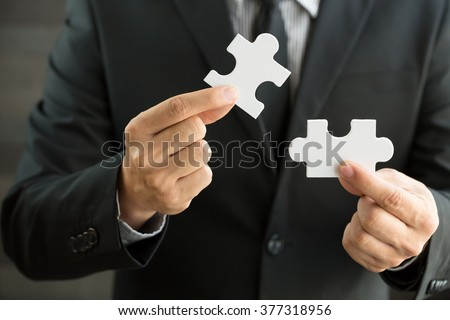 Businessmen holding two jigsaw to connect