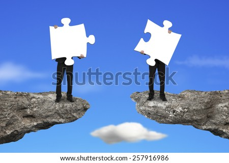 Businessmen holding two white jigsaw puzzles to connect on the cliff with sky background - stock photo
