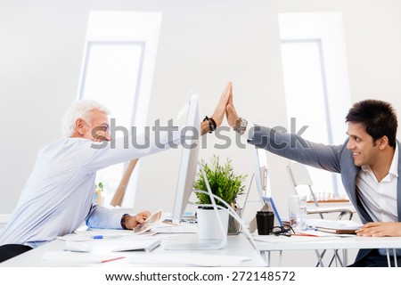 Businessmen in office cheering at their success - stock photo
