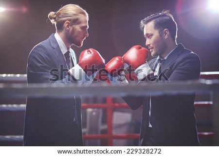 Businessmen in suits and boxing gloves fighting on boxing rink - stock photo