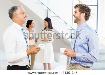 Businessmen interacting during a break time in the office - stock photo