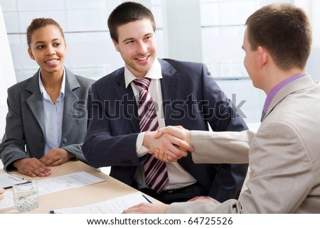 Businessmen joining hands in an office